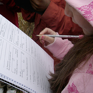 Girl recording observations in a notebook