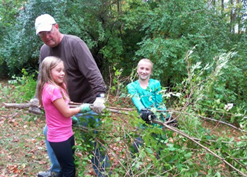 Girls working with community member to clear brush