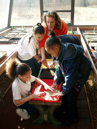 Mary leads students in greenhouse