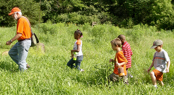 Volunteer Educator leads young learners through the prairie.